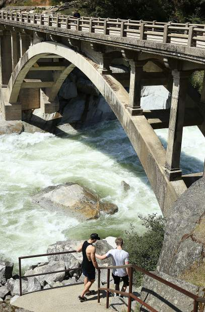 A pair of young men inspect the high flows of the South Yuba River for themselves Friday afternoon near the old Highway 49 bridge.