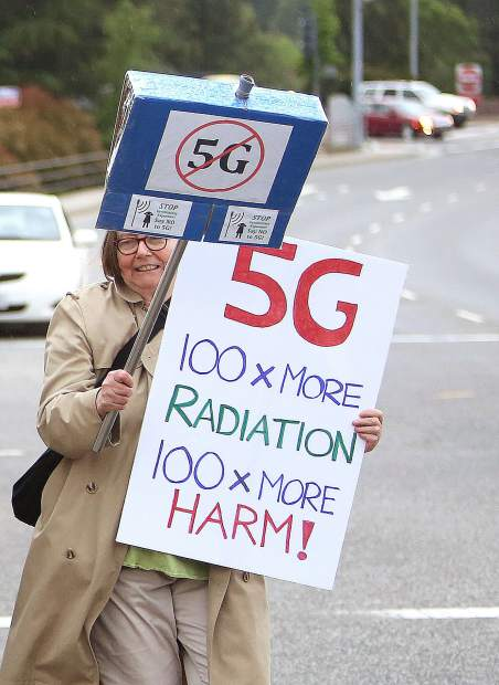 Folks hold signs protesting the development and institution of 5G cellular networks.