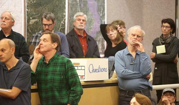 Cascade Shores and Banner Mountain residents stand around a question box as they listen to a wildfire evacuation and preparedness meeting hosted by local fire and police first responders.