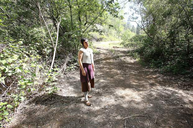 Ember Amador stands in a swath of the 32 acre land allocated to California Heritage: Indigenous Research Project recently bulldozed in efforts to help create access to abandoned camps for cleanup on the property.