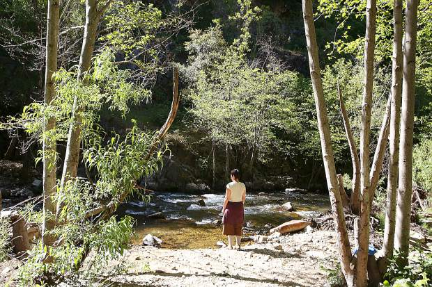 California Heritage: Indigenous Research Project Executive Assistant Ember Amador stands on the edge of Deer Creek near Nevada City where 32 acres of land was acquired. Plans for cleanup days as well as future usage are currently in the works.