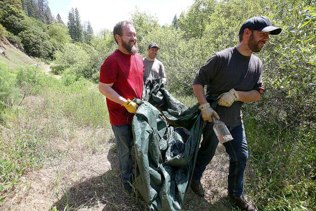 Drew Albrecht, Saxon Thomas and brother Colin Thomas, who are members of the local Nisenan tribe, help haul out a particularly smelly tarp full of refuse pulled from the remnants of one of many homeless encampments on the 32-acre former Champion Mine property.