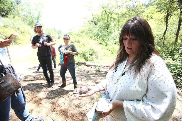 Nisenan tribal spokesperson Shelly Covert shows off a couple rocks of interest found during the cleanup Thursday morning.