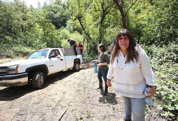 Nisenan Tribal spokesperson Shelly Covert smiles as truck loads of trash are pulled from the property recently donated to her organization, California Heritage: Indigenous Research Project, Thursday morning off of Champion Mine Road.