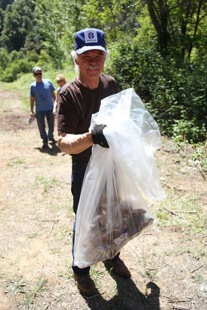 A volunteer proudly holds a bag of trash picked up during Thursday's CHIRP property clean up.