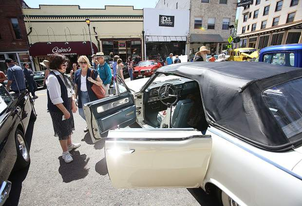 San Martin's Marilyn Carr shows off the suicide doors of her 1963 Lincoln Continental on display in front of the Holbrooke Hotel.