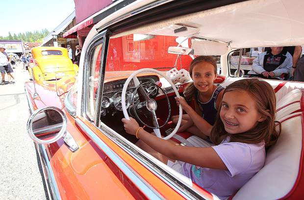 Twins Leah and Reagan Johnstone pose inside of a 1959 Buick LeSabre owned by Browns Valley's Dave Stipp during the 2019 Grass Valley Car Show.