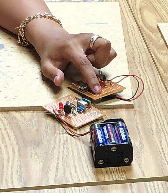 Students at Sierra Montessori Academy at the school are highlighting batteries for their phone chargers they created last week as part of project, charged up, with volunteers from the American Association of University Women.