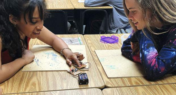 Tatiana Robinson (left) and Avery Holcomb (right) analyze their phone charger.