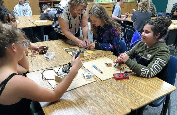 Students gather around their phone chargers, tinkering with them, with instruction from volunteer, Deb Sabo.