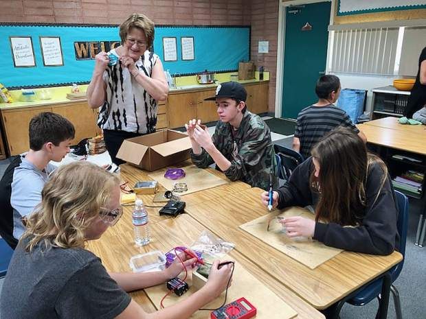 Jasmin Pratt (grade 8), Caitlyn College (grade 7), David Nofsinger (grade 8) and Chase Kangas (grade 8) analyze phone chargers with women's organization treasurer, Deb Sabo.
