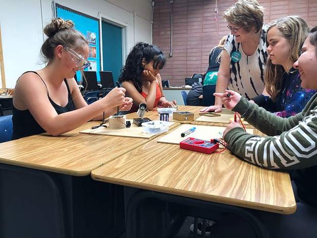 Deb Sabo oversees Karma Plas (grade 7), Arianna Howe (grade 7), Avery Holcomb (grade 8) and Tatiana Robinson (grade 8) analyzing their recent creations.