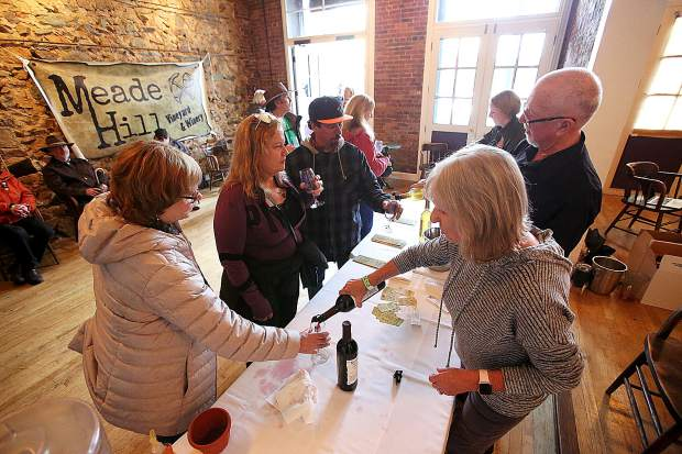 Meade Hill Vineyard and Winery's Pamie Lacefield pours wine for attendees of Saturday's Foothills Celebration tasting event from inside the Holbooke Hotel. Meade Hill is a new winery in Smartsville and was one of nearly 50 area businesses offering samplings of food and wine.
