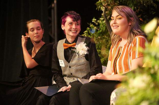 Scarlett Jones (from left), Guage Johnson, and Dejah Thurman listen to the stories of other fellow Friendship Club graduates during Thursday's graduation gala.