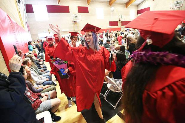 Grads wave to their friends and family following Thursday's Sierra College commencement ceremony, held indoors due to lingering showers.