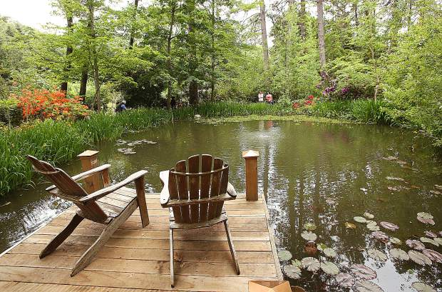 A pair of lawn chairs seem to invite users to spend some time around the pond that is central to the Ruland's family garden, a highlight of the 2019 Spring Garden Tour.