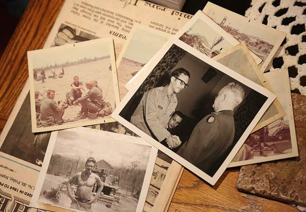 A collection of photos from Bill Larsen's time as a soldier in Vietnam are displayed on his coffee table.