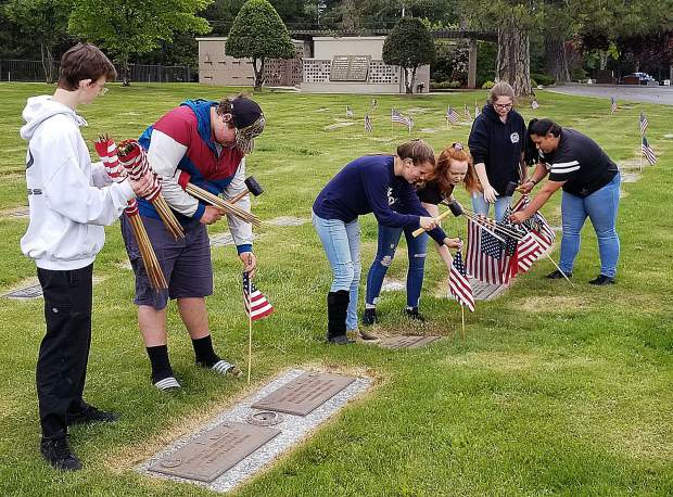 Two dozen Nevada Union High School FFA members spent hours this week placing American flags at military headstones in four local cemeteries.