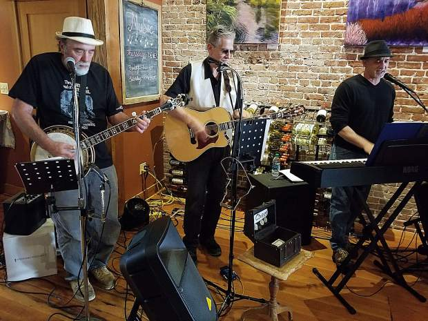 Ken Bigham (center) played guitar and sang at his own 70th birthday party with bandmates Paul Siese on banjo (left) and Kelly Nevius on keyboard.