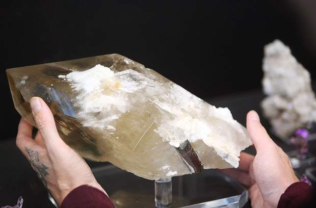 Aaron Robin, owner of Crystal Junction, places a large and elaborate quartz crystal back on the display shelf.