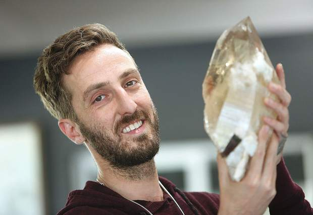 Aaron Robin, owner of Crystal Junction in Nevada City, happily holds one of his large crystals that are on display and for sale at his Argall Way crystal shop.