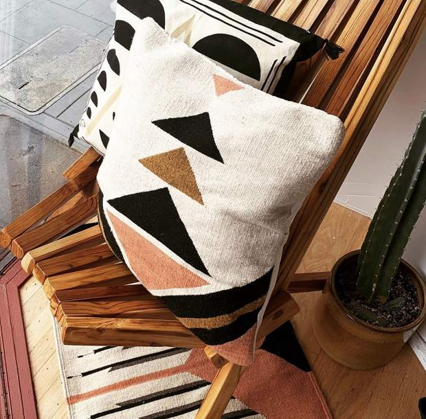 Pillows and a rug designed by HŌM, a modern home decor company owned by Leif Wold and Danielle Rubio of Rough and Ready.