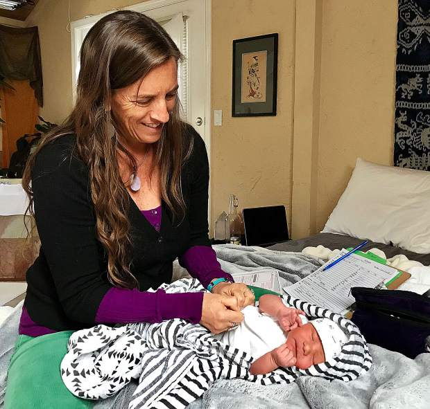 Midwife Cindy Foxfoot examines a newborn.
