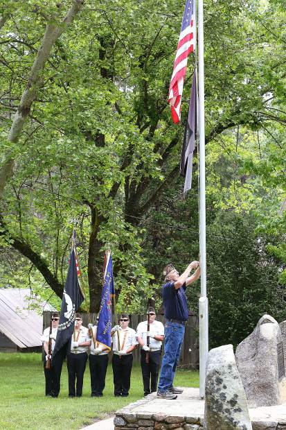 The American flag is raised and then lowered to half staff during the beginning of the Pioneer Park Memorial Day ceremony Monday morning.