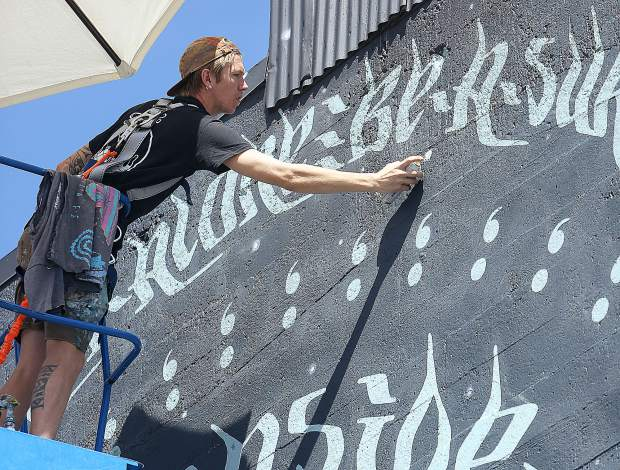 Mural artist Miles Toland adds details to the