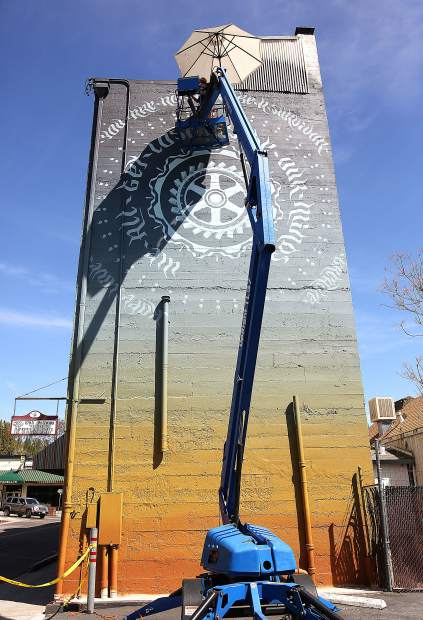 Toland works on the unfinished mural last week on the Everhart Hotel in downtown Grass Valley.