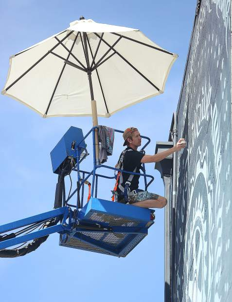 Mural artist Miles Toland works on the details of the mural titled