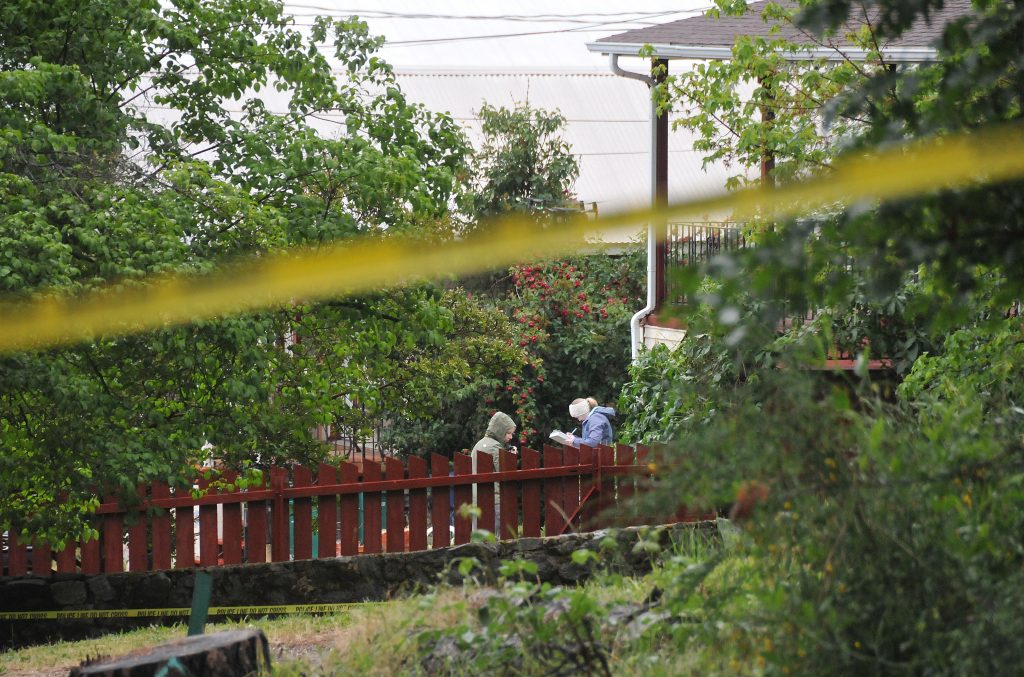Crime scene investigators take notes from the front of the home on Glenwood Drive in Grass Valley where two people were found shot to death Monday night.