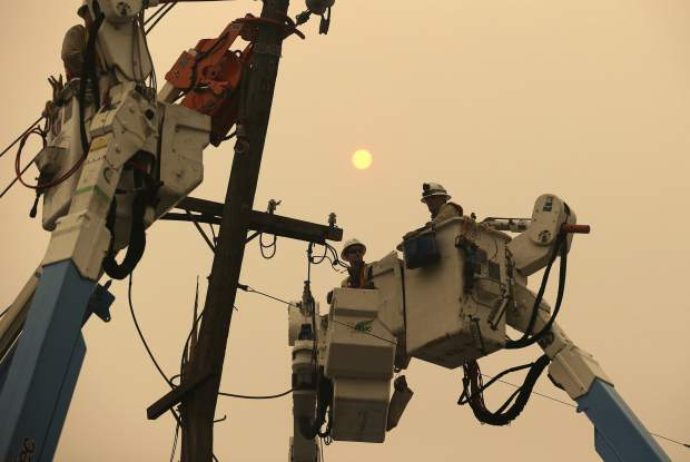 FILE - In this Nov. 9, 2018 file photo, Pacific Gas & Electric crews work to restore power lines in Paradise, Calif. Some investors call PG&E the first climate change bankruptcy. It filed for Chapter 11 protection earlier this year due to potential liabilities piling up following devastating wildfires in northern California. (AP Photo/Rich Pedroncelli, File)