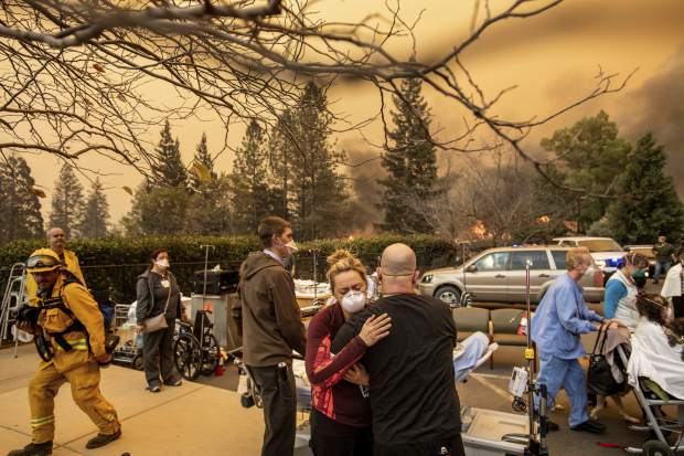 FILE - This Nov. 8, 2018, file photo shows Nurse Cassie Lerossignol hugs as coworker as the Feather River Hospital burns while the Camp Fire rages through Paradise, Calif. California fire authorities say that Pacific Gas and Electric equipment was responsible for the deadliest and most destructive wildfire in state history. Cal Fire said in a press release issued Wednesday, May 15, 2019, that electrical transmission lines in the Pulga area sparked the Nov. 8 fire that wiped out most of the town of Paradise and killed 85 people. (AP Photo/Noah Berger, File)