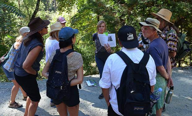 Laura Petersen, center, huddles up with a group of hikers on a Hiking For Good excursion. Hiking for Good has teamed up with Outlandish Experiences, getting people outdoors while giving back to environmental and social justice organizations.