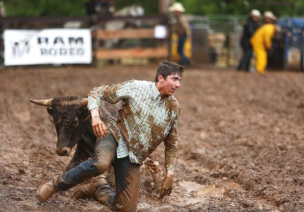 A steer wrestler gets up from a mud filled arena during the  Penn Valley Rodeo.