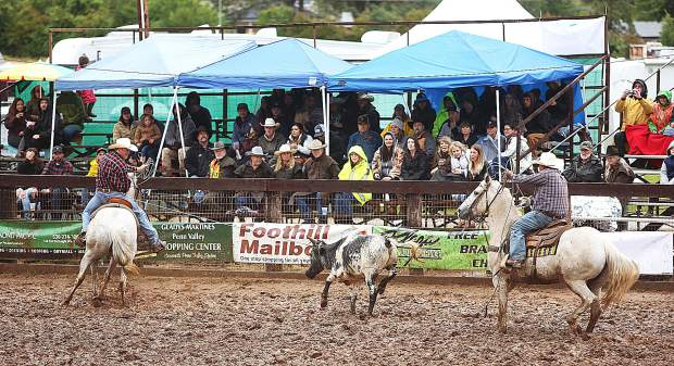 A pair of team ropers perform in front of the crowd at the Penn Valley Rodeo in between Saturday's rain showers.
