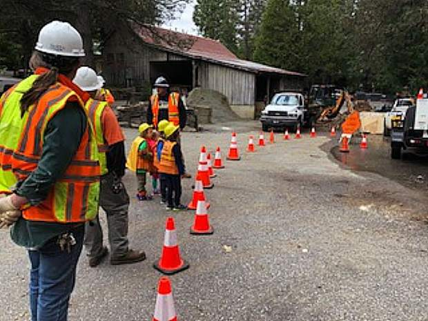 Public works officials demonstrate for preschool students how they operate their equipment.