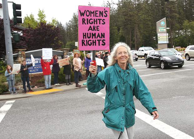 A woman holds a pro-choice sign as she crosses Sutton Way during Tuesday's rally.