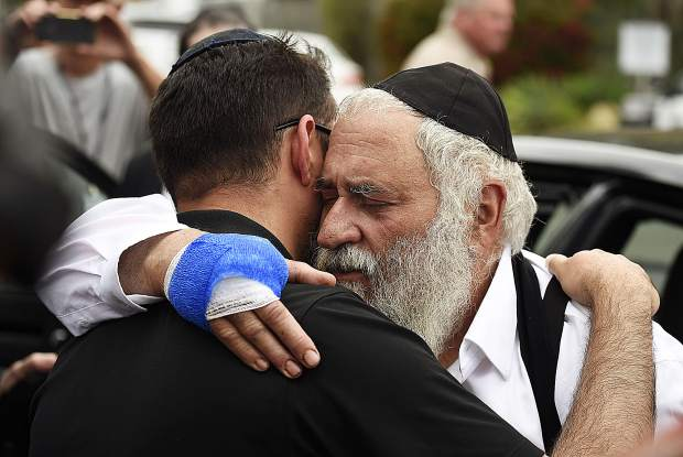 Rabbi Yisroel Goldstein, right, is hugged as he leaves a news conference at the Chabad of Poway synagogue.