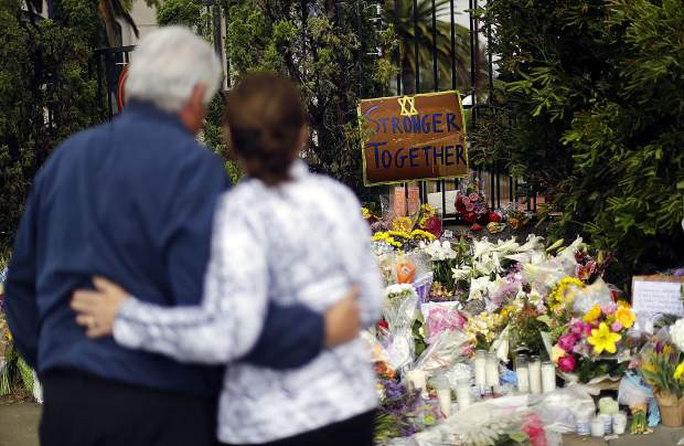 A couple embrace near a growing memorial across the street from the Chabad of Poway synagogue in Poway, Calif., on Monday,, April 29, 2019. A 19-year-old gunman opened fire on Saturday as about 100 people were worshipping exactly six months after a mass shooting in a Pittsburgh synagogue, killing one and injuring more. (AP Photo/Greg Bull)