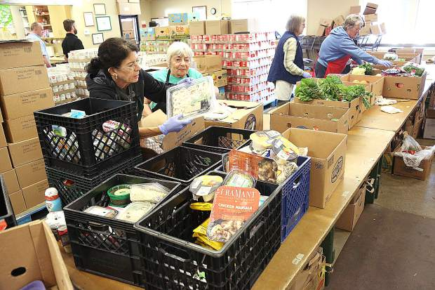 Workers and volunteers work to fulfill food orders for those in need Wednesday morning from Interfaith Food Ministry's Henderson Street location in Grass Valley.