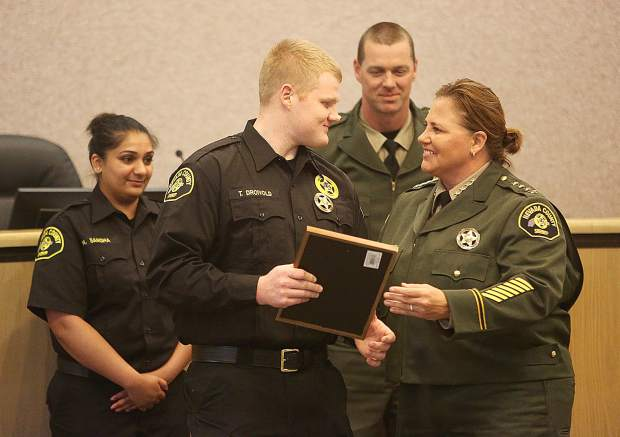 Nevada County Sheriff Shannan Moon hands Tyler Droivold a proclamation following his badge pinning as a correctional officer.