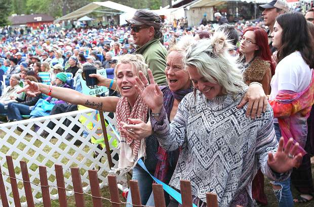 A trio of enthusiastic festival goers dance to the music of the main stage Saturday evening at the Strawberry Music Festival.