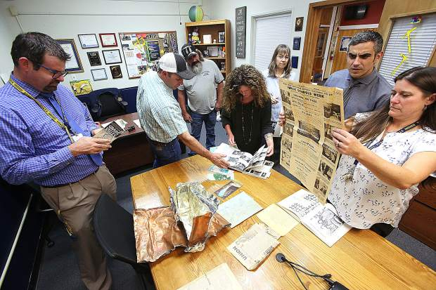 Nevada Union High School staff, along with a couple members of Hansen Brothers Enterprises, inspect the contents of a time capsule unearthed from the high school campus during the recent improvements to the school's parking lot. High school year books from the 50s and 60s, as well as newspaper clippings, local maps, and other memorabilia were found inside a watertight metal box.