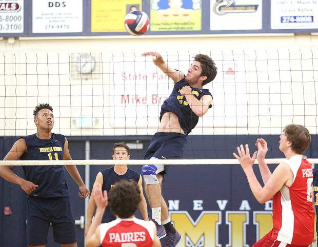 Nevada Union senior Jordan Mills (23) spikes the ball over the net for a point against the Carmel Padres Tuesday at the Albert Ali Gymnasium in Grass Valley.