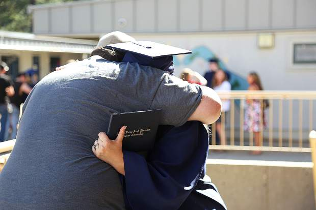 A family member gives a heartfelt embrace to his wife following the adult education graduation Tuesday at Nevada Union High School.