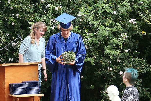 Graduating Bitney Prep student Rex Des Tombe presents a cactus as the senior gift to a representative of the junior class, with the message that even though we can be a bit prickly, we are also succulent.
