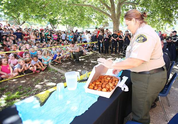 Nevada County Sheriff Shannan Moon eyes her box of over 100 donut holes that she and members of NCSO pledged to eat as part of a go fund me fundraiser in place of the Blue Marble Jubilee which was cancelled due to an unfounded threat.