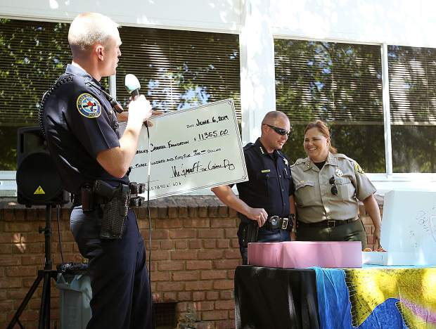 Grass Valley Chief of Police Alex Gammelgard shows off a check for $11,355 raised through a go fund me account in place of the cancelled Blue Marble Jubilee which was canelled due to an unfounded threat. Nevada City Chief of Police Chad Ellis and Sheriff Shannan Moon also helped to eat donut holes during the eating challenge.